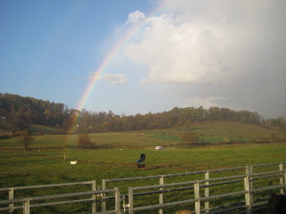 The sun shines through a rainbow over the farm.